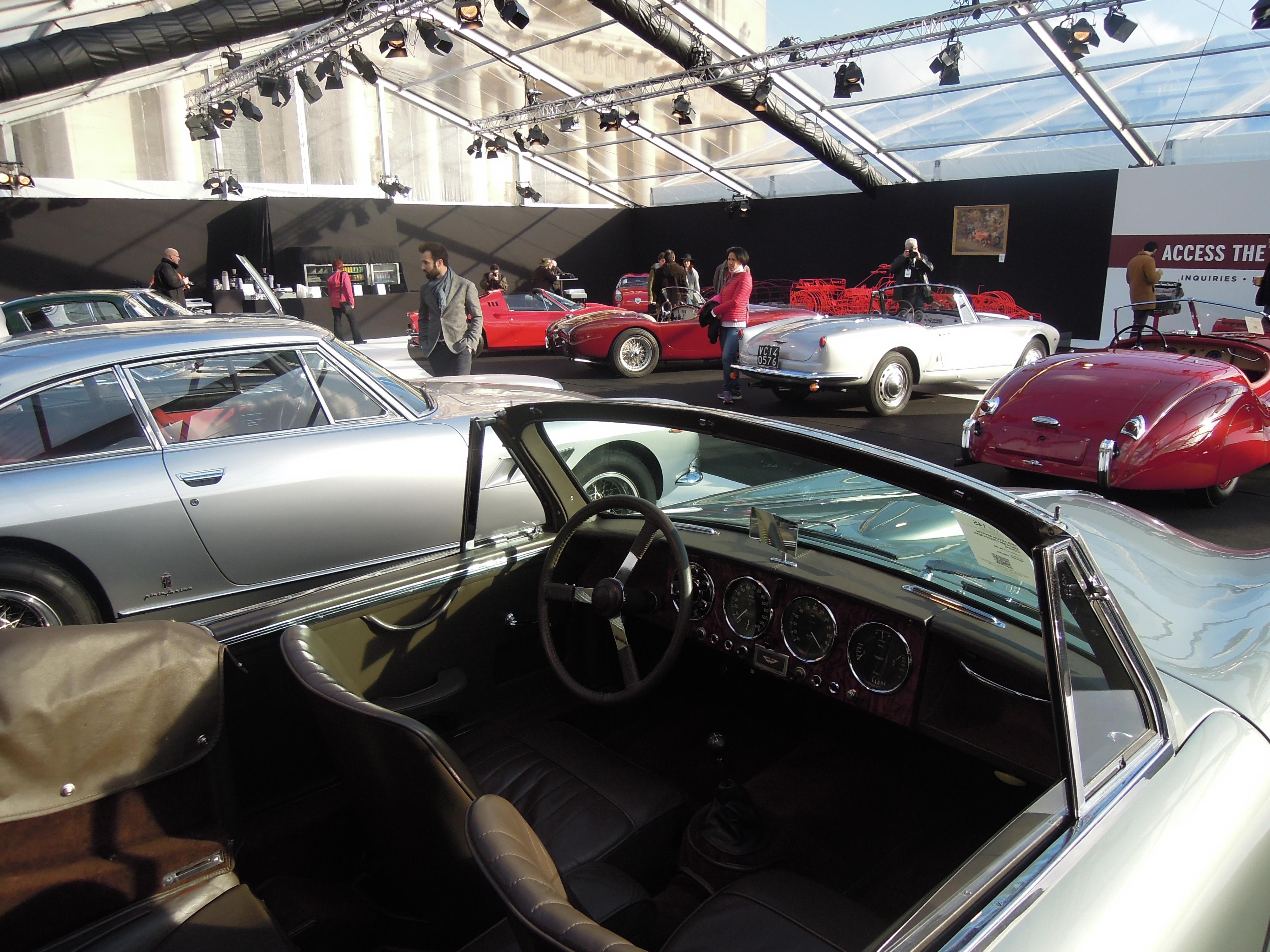 Vue d'ensemble de quelques autos proposées : au premier plan, l'habitacle d'une Aston Martin DB2/4.